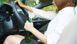 Drunk woman driving and holding beer bottle inside a car